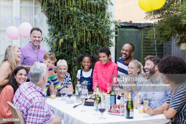 multi generation family enjoying birthday party at garden patio table - cef do not delete stock pictures, royalty-free photos & images
