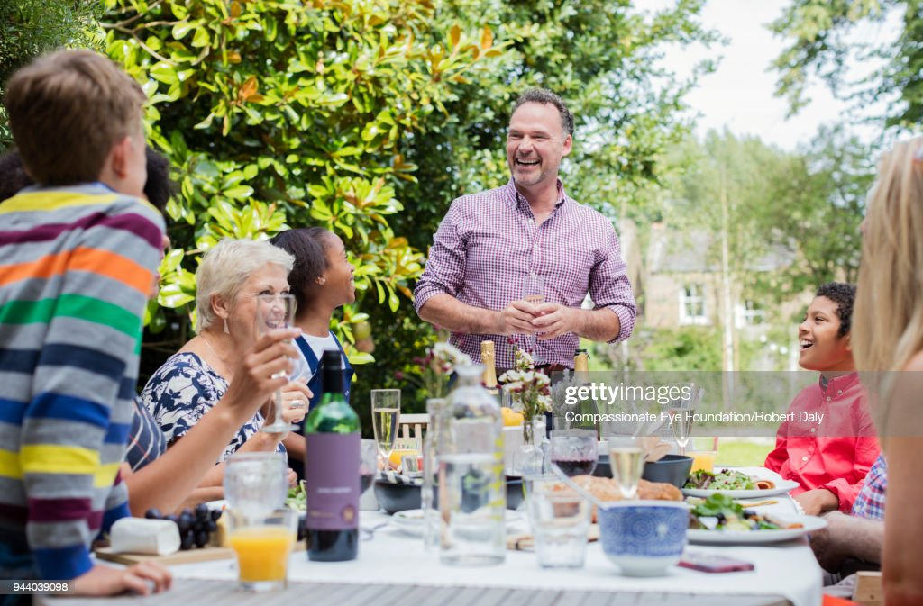 Multi generation family enjoying lunch at garden patio table : Stock Photo