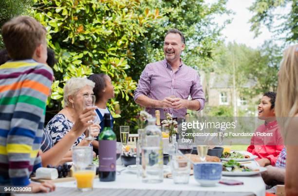 multi generation family enjoying lunch at garden patio table - maniche arrotolate foto e immagini stock