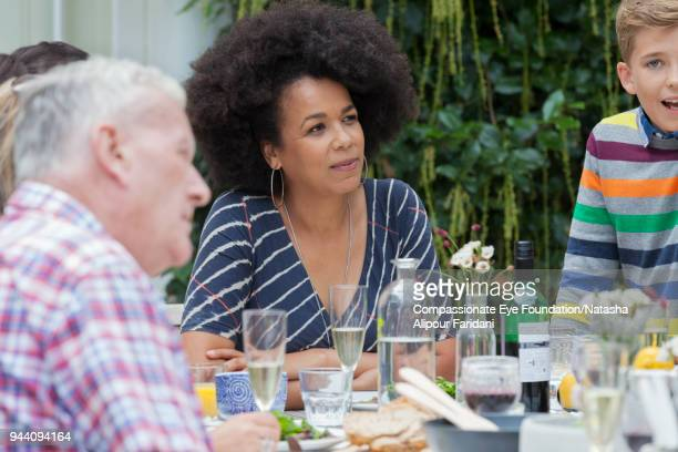 """multi generation family enjoying lunch at garden patio table - """"compassionate eye"""" stock pictures, royalty-free photos & images"""