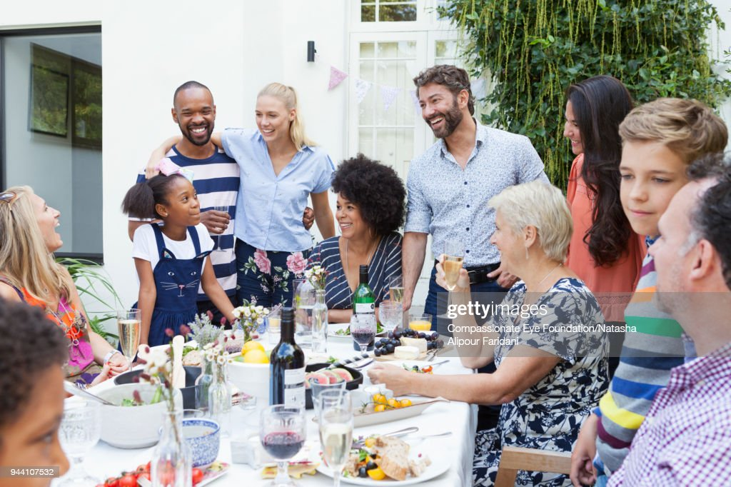 Multi generation family enjoying lunch party at patio table : Stock Photo