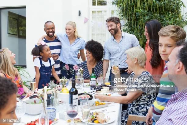 multi generation family enjoying lunch party at patio table - disruptagingcollection stock photos and pictures