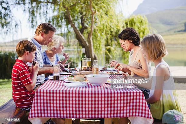 multi generation family having a picnic - picnic table stock pictures, royalty-free photos & images