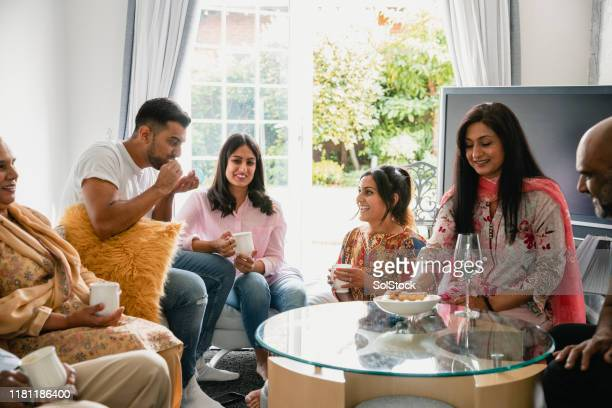 multi generation family having a snack - indian ethnicity stock pictures, royalty-free photos & images