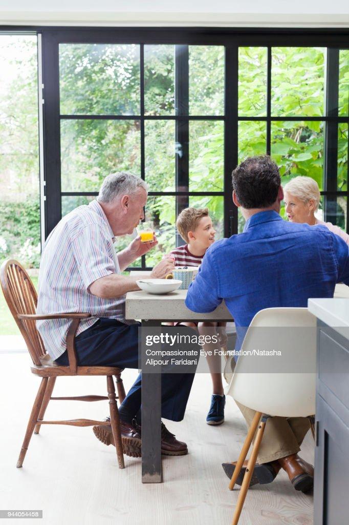 Multi generation family having breakfast at dining table : Stock Photo