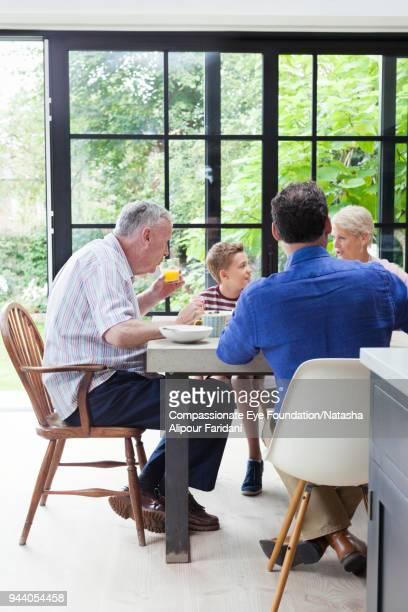 Multi generation family having breakfast at dining table
