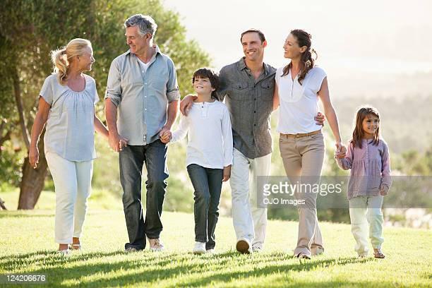 Multi-Generationen-Familie holding Hände und Spaziergang im park