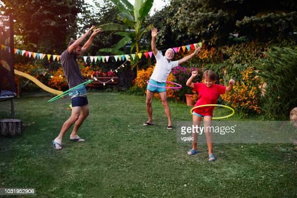 Multi generation family hula hooping in backyard