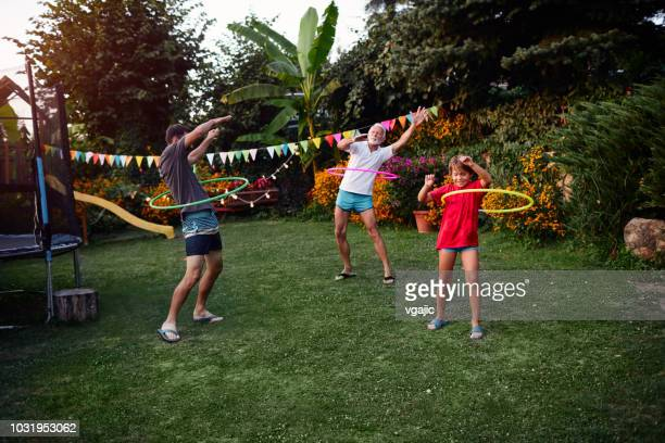multi generation family hula hooping in backyard - polynesian dance stock photos and pictures