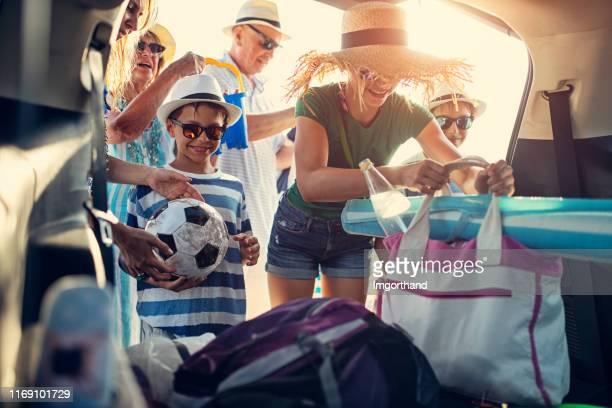 mehrgenerationenfamilie packt auto. - autoreise stock-fotos und bilder