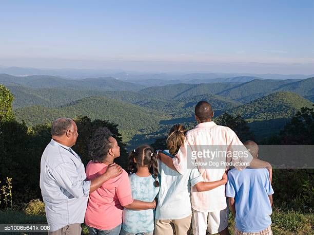 Multi generation family on hill, looking at view, rear view