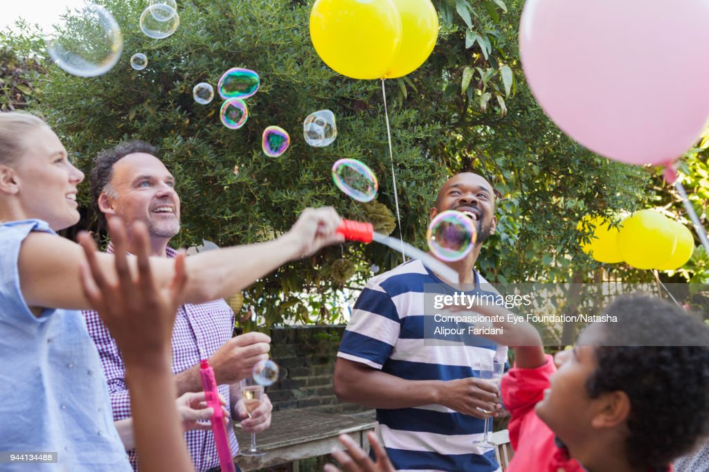 Multi generation family party on garden patio playing with bubbles and balloons : Stock-Foto