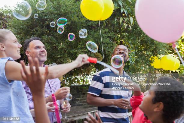 Multi generation family party on garden patio playing with bubbles and balloons