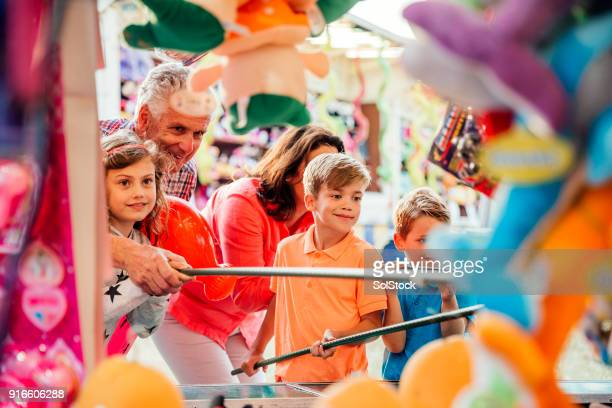 multi generation family playing hook a duck - carnival celebration event stock photos and pictures