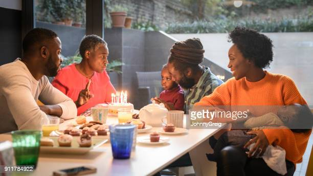 multi generation family sitting around dinner table with birthday cake and food - afro caribbean ethnicity stock pictures, royalty-free photos & images