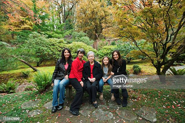 multi generation family sitting in park - great grandmother stock pictures, royalty-free photos & images