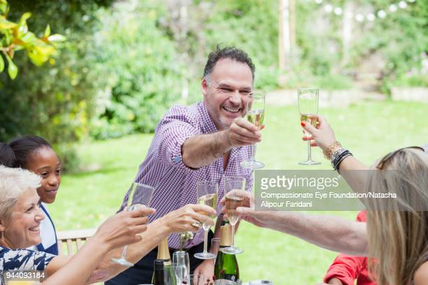 Multi generation family toasting champagne glasses at birthday party on garden patio