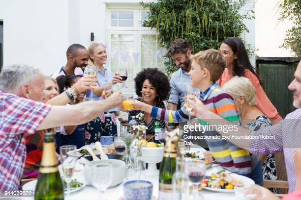"""multi generation family toasting with champagne glasses at garden patio table - """"compassionate eye"""" stock pictures, royalty-free photos & images"""