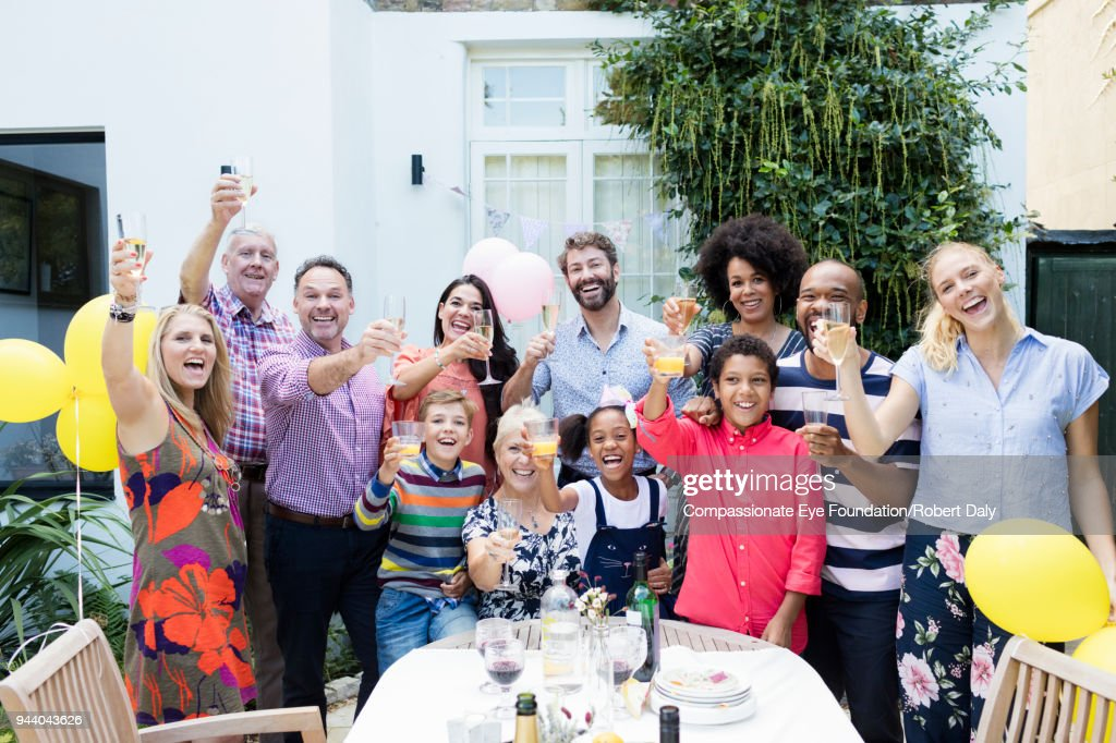 Multi generation family toasting with champagne glasses at party on garden patio : Stock Photo