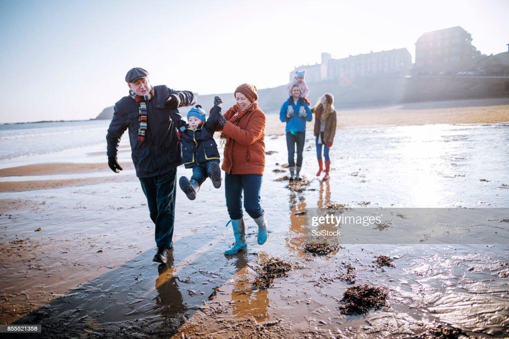 Multi- Generation Family Walking Along the Beach : Stock Photo