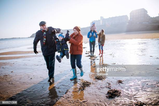 multi- generation family walking along the beach - old stock photos and pictures