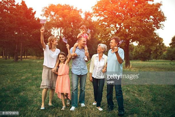 multi generation family walking in a park with us flags. - fourth of july stock photos and pictures