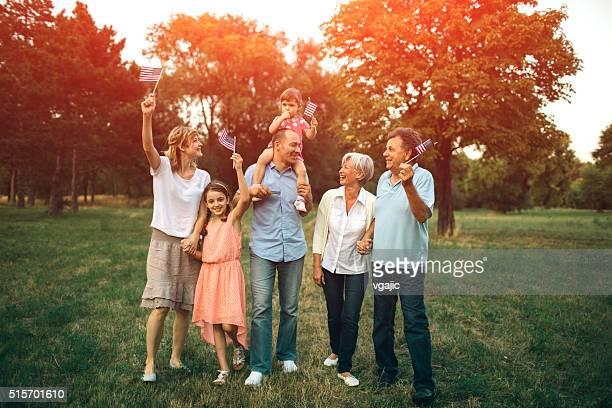Multi-generazione famiglia A piedi In un parco con noi bandiera.