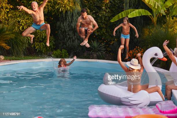 Multi generation Having Fun Around The Backyard Pool
