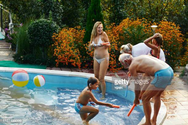 multi generation having fun around the backyard pool - cochlear implant stock pictures, royalty-free photos & images