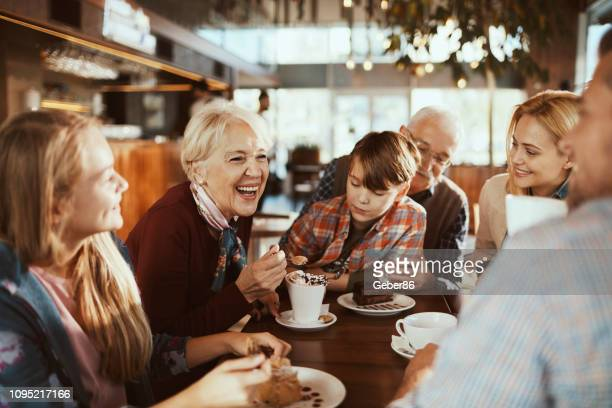 multi generational family in a cafe - restaurant stock pictures, royalty-free photos & images