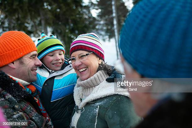 Multi generational family in snowy landscape, smiling, close-up