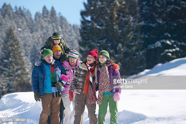Multi generational family walking in snow covered winter landscape