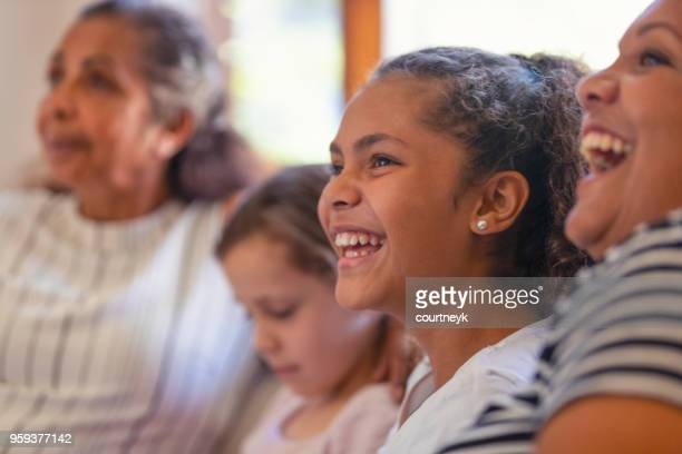 multi generational women on the sofa. the young girls are sisters. - diversity stock pictures, royalty-free photos & images