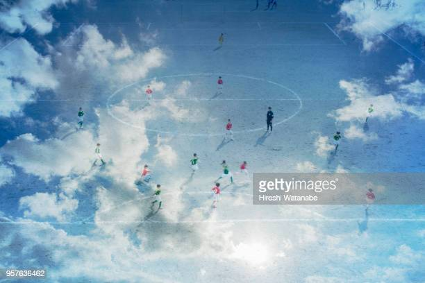 Multi layered, boys playing soccer game in the cloud