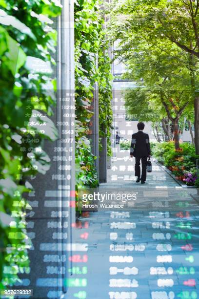 Multi layered, walking businessman with stock index