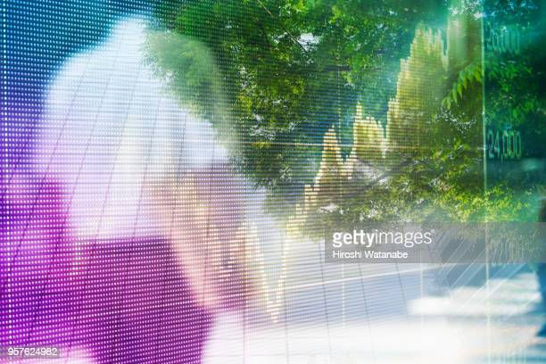 Multi layered, walking businessman with stock market graph