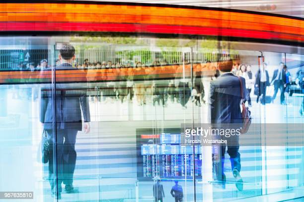 Multi layered, walking businessman with Tokyo Stock Exchange