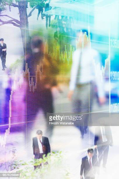 Multi layered, walking businessmen with stock market graph