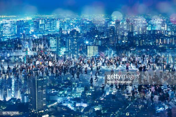 Multi layered, walking people on night cityscape
