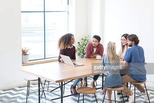Multi racial business people using laptop in meeting