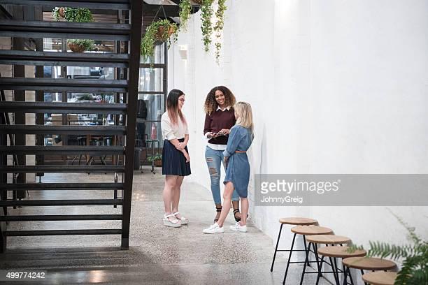 Multi racial businesswomen talking by staircase in modern office