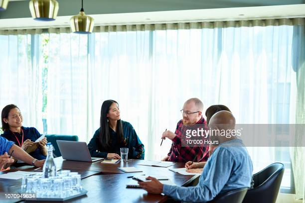 multi racial colleagues in conference room - marketing stock pictures, royalty-free photos & images