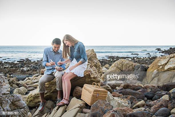 Multi Racial Couple Eating Sushi at the Beach