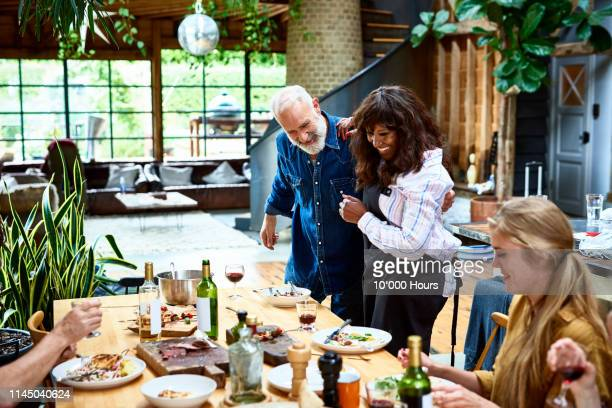 multi racial couple hosting relaxed dinner party at home - gast stockfoto's en -beelden