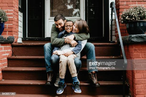 multi racial family photos with adoptive son big hug - adoptie stockfoto's en -beelden