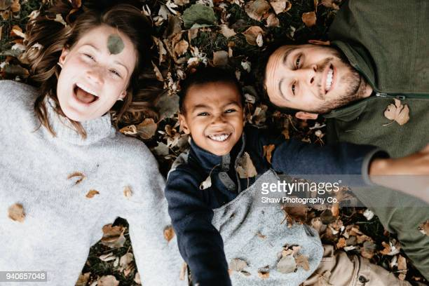 Multi racial family photos with adoptive son in fall leaves