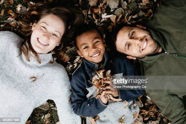 multi racial family photos with adoptive son in fall leaves - adoptie stockfoto's en -beelden