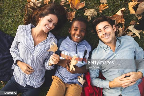 familia multiracial con niños adoptivos pasando tiempo juntos en el parque - adopción fotografías e imágenes de stock