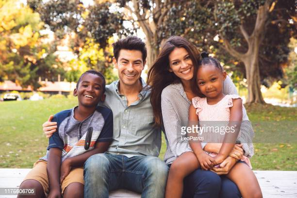 multi racial family with adoptive children spending time together at the park - mixed race person stock pictures, royalty-free photos & images