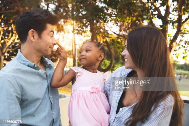 multi raciale familie met adoptiekinderen samen tijd doorbrengen in het park - adoptie stockfoto's en -beelden